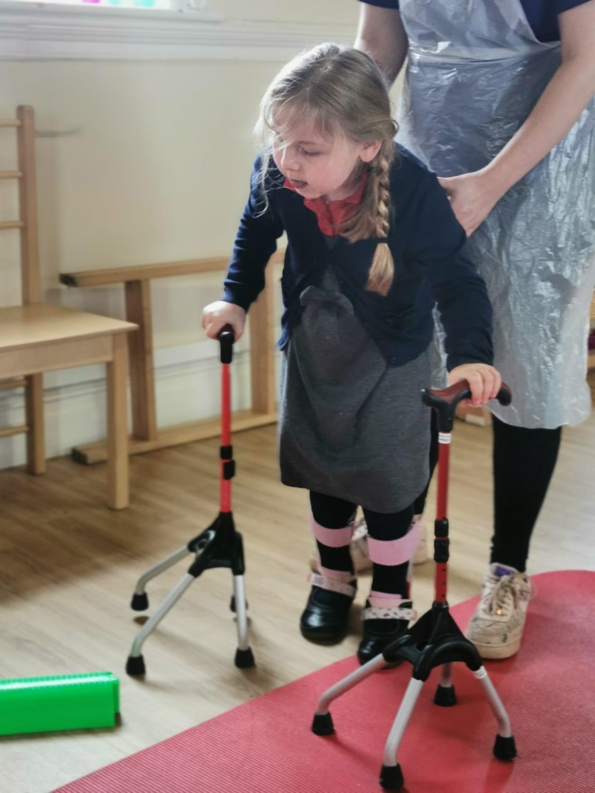 A little girl with walking sticks at Megan Baker House